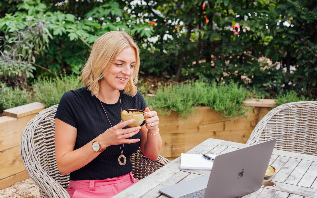 Woman sat drinking tea looking at laptop